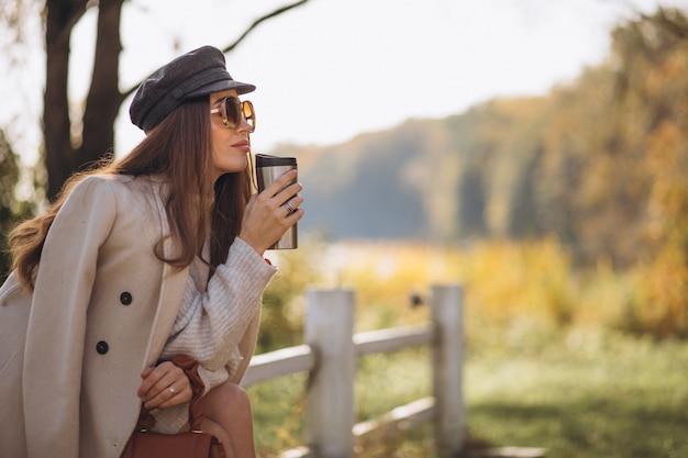 Schöne frau, die heißen tee draußen trinkt