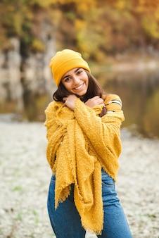 Schöne frau, die herbsttag genießt. schönheit und mode. herbstmode und lifestyle. hübsche frau, die warme herbstkleidung, mütze und gelben schal trägt. herbststimmung. modische frau im freien.