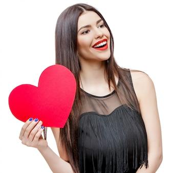 Schöne frau, die herzförmige valentinsgrußkarte hält und lächelt