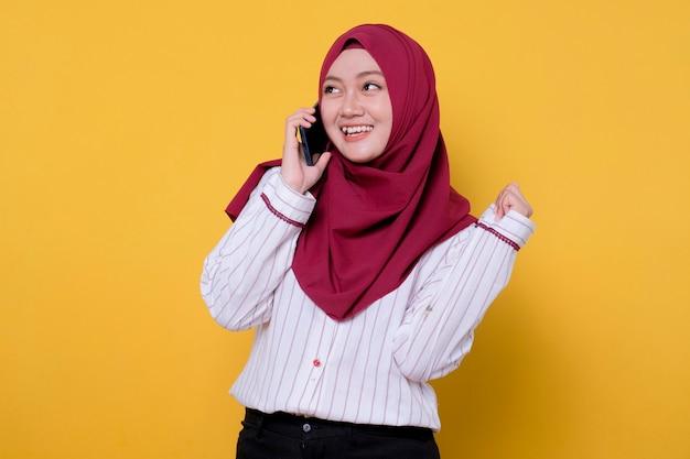 Schöne frau, die hijab trägt, der unter verwendung des lächelnden und fröhlichen mobiltelefons spricht