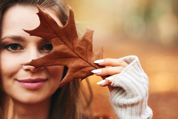 Schöne frau, die ihr gesicht mit herbstblättern bedeckt