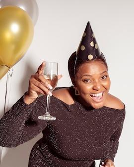 Schöne frau, die ihr glas champagner zeigt
