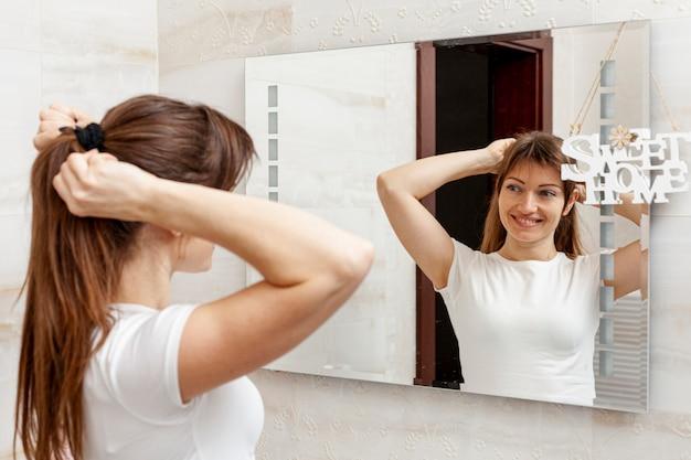 Schöne frau, die ihr haar im spiegel anordnet