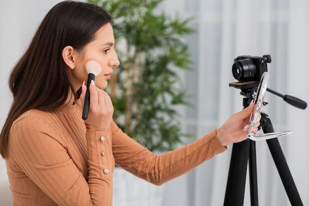 Schöne frau, die ihr make-up auf kamera tut