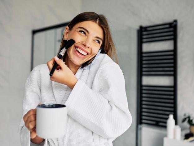 Schöne frau, die ihr make-up macht