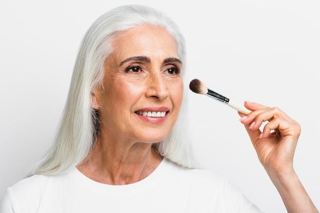 Schöne frau, die ihr make-up tut