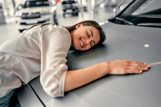 Schöne frau, die ihre liebe zu einem auto in einem autohaus umarmt und zeigt.