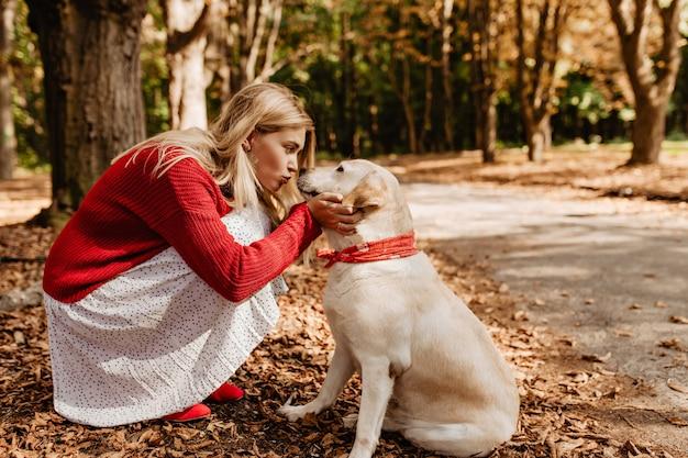 Schöne frau, die ihren entzückenden schönen hund küsst. schönes mädchen im roten pullover und im weißen kleid, die liebe mit einem haustier teilen.