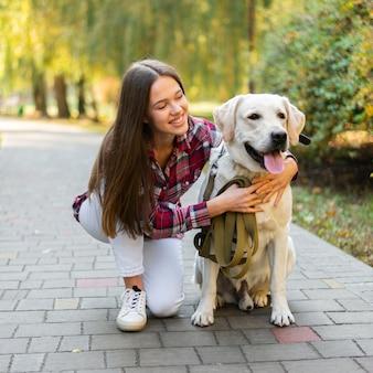 Schöne frau, die ihren hund anhält