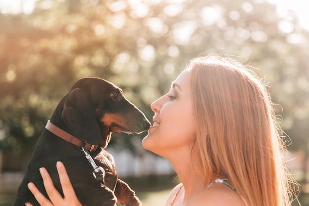Schöne frau, die ihren netten hund küsst