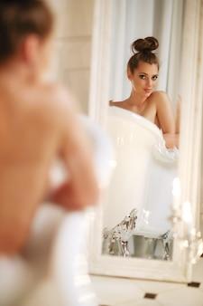 Schöne frau, die im badezimmer aufwirft