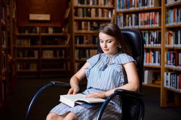 Schöne frau, die im bequemen sessel sitzt und buch liest