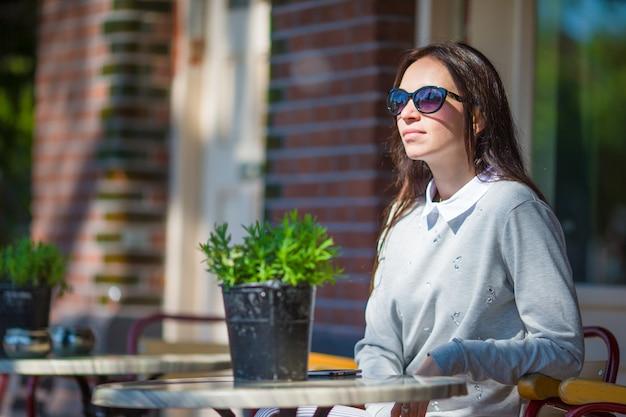 Schöne frau, die im freienkaffee an der europäischen stadt sitzt