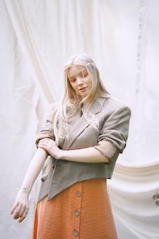 Schöne frau, die im garten, im orangefarbenen kleid und in der jacke während des tages denkt.