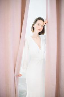 Schöne frau, die im langen weißen kleid im perlenzimmer steht und schaut.