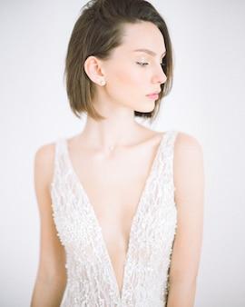 Schöne frau, die im langen weißen kleid im raum mit weiß steht und schaut
