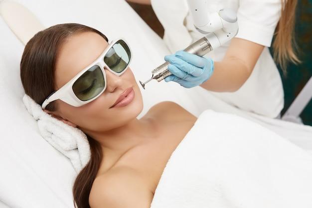 Schöne frau, die im medizinischen kosmetikzentrum liegt und laserverfahren empfängt, hübsche frau im spa, die gesichtsbehandlung mit kosmetikerin hat