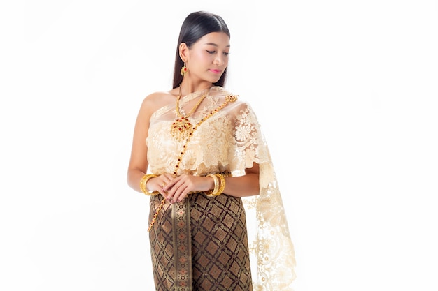 Schöne frau, die im nationalen traditionellen kostüm von thailand lächelt. auf weiß zu isolieren.