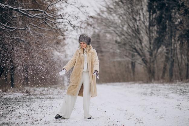 Schöne frau, die im park voller schnee spazieren geht
