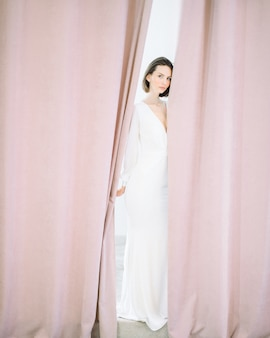 Schöne frau, die im perlenzimmer im langen weißen kleid steht und schaut.