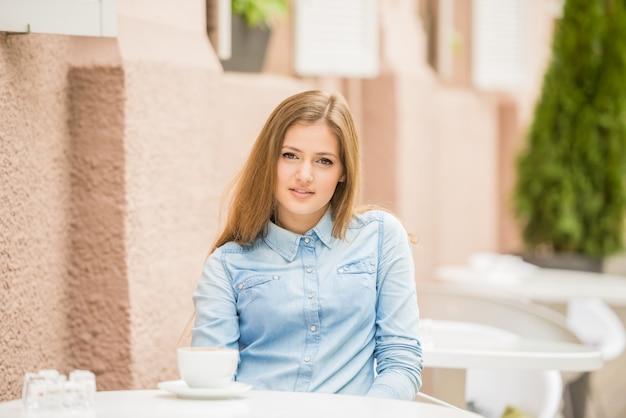 Schöne frau, die im sommerkaffee mit tasse kaffee sitzt.