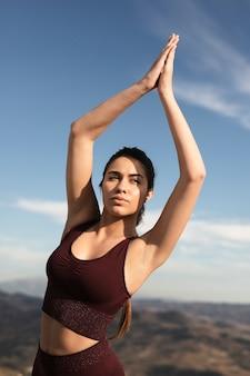 Schöne frau, die im sonnenlicht yoga tut