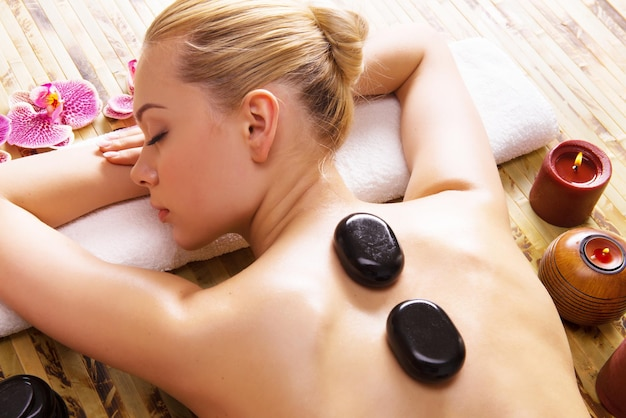 Schöne frau, die im spa-salon mit heißen steinen auf körper entspannt. schönheitstherapie