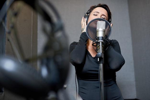 Schöne frau, die im studio singt