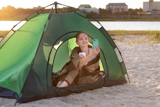 Schöne frau, die im zelt sitzt und ein foto macht. camping in der nähe von wasser. urlaub im freien.