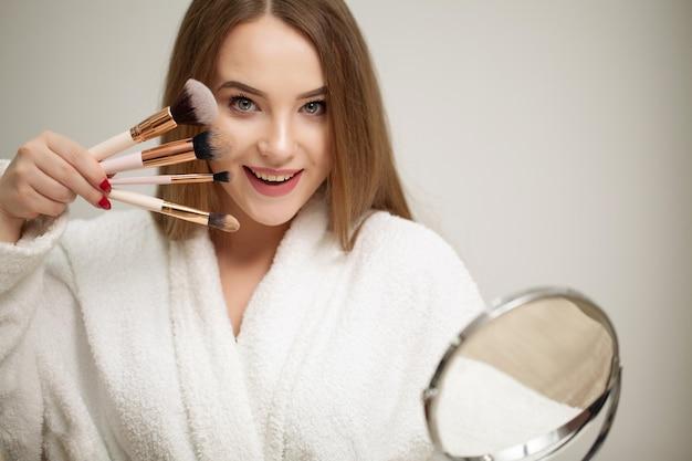 Schöne frau, die in den spiegel schaut und kosmetik mit einem großen pinsel anwendet.