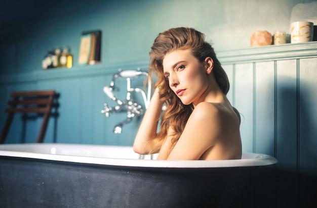 Schöne frau, die in der badewanne sich entspannt