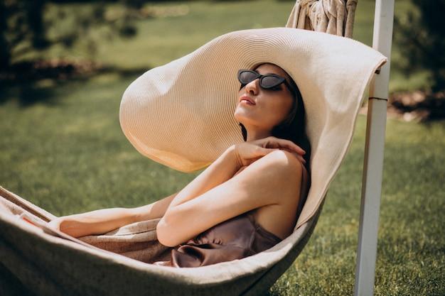 Schöne frau, die in der hängematte liegt und großen sonnenhut trägt