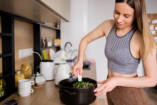 Schöne frau, die in der modernen küche kocht