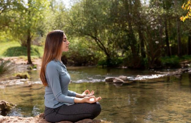 Schöne frau, die in der natur meditiert