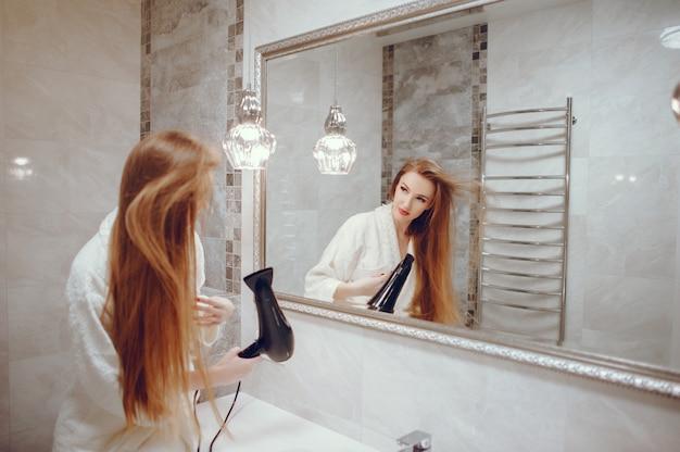 Schöne frau, die in einem badezimmer steht