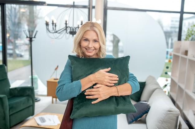 Schöne frau, die in einem hellen geräumigen möbelhaus steht, das ein grünes dekoratives kissen umarmt, in der ausgezeichneten stimmung.