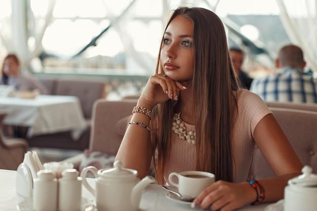 Schöne frau, die in einem restaurant sitzt und tee trinkt.