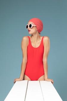 Schöne frau, die in einem roten badeanzug aufwirft