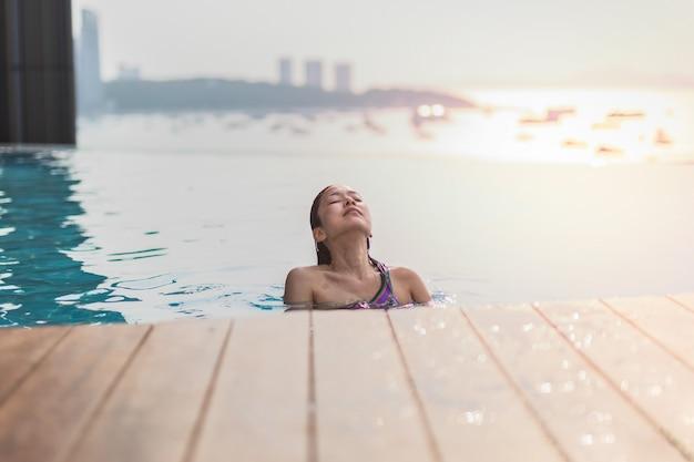 Schöne frau, die in einem schwimmbad unter dem sommerlicht lächelt Premium Fotos