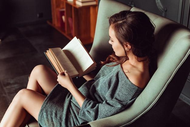Schöne frau, die in einem stuhl sitzt und ein buch liest