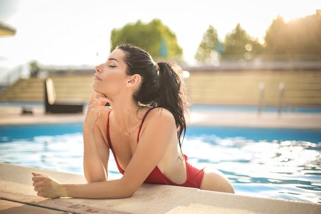 Schöne frau, die in einem swimmingpool kühlt