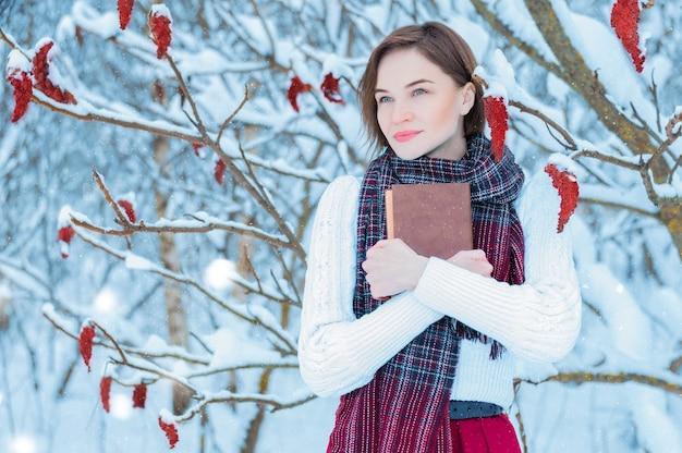 Schöne frau, die in einem winterwald mit einem buch in ihren händen steht.
