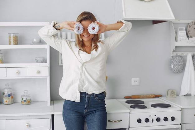 Schöne frau, die in einer küche mit krapfen steht