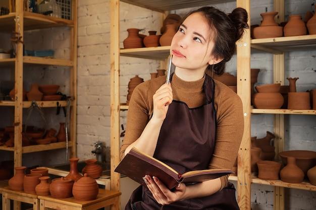 Schöne frau, die in einer töpferwerkstatt in einem notizbuch sitzt und schreibt. der töpfer schreibt ideen auf den hintergrund eines gestells mit tontöpfen und vasen. inspiration und muse.