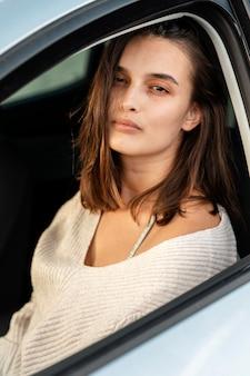 Schöne frau, die in ihrem auto während eines straßenausfluges aufwirft