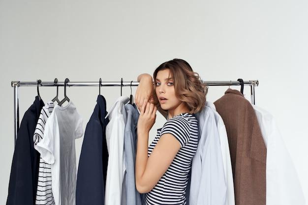 Schöne frau, die isolierten hintergrund im bekleidungsgeschäft anprobiert