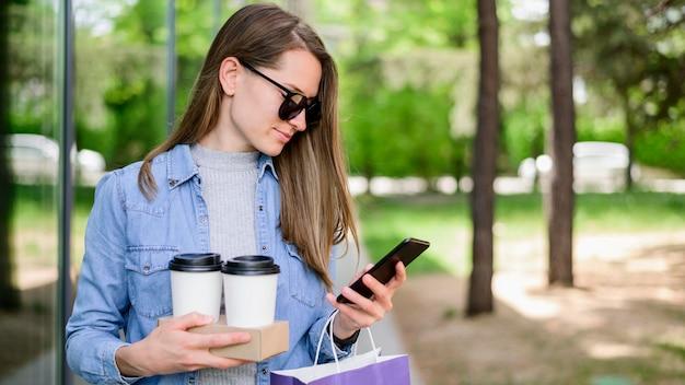 Schöne frau, die kaffee trägt, während telefon überprüft