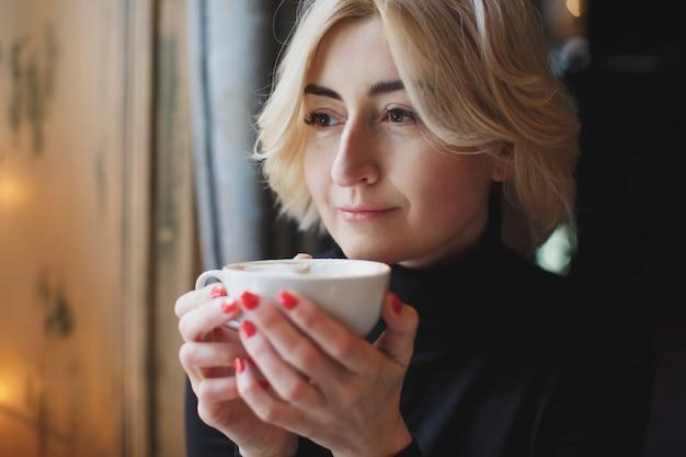 Schöne frau, die kaffee trinkt
