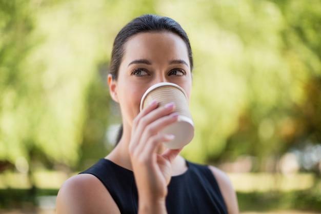Schöne frau, die kaffee vom wegwerfbecher trinkt