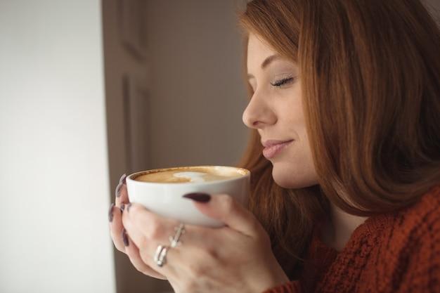 Schöne frau, die kaffeetasse am fenster hält